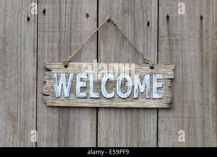 Rustic wood welcome sign hanging on wooden background - Stock Photo