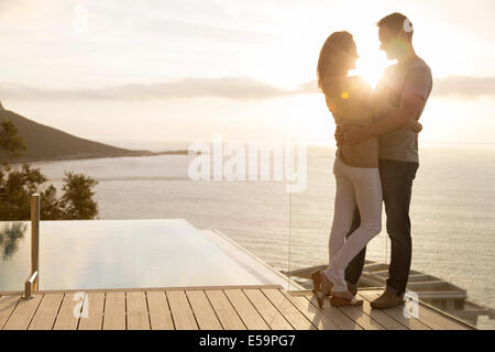 Couple on wooden deck overlooking ocean - Stock Photo
