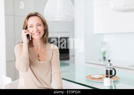 Woman talking on cell phone at breakfast table - Stock Photo