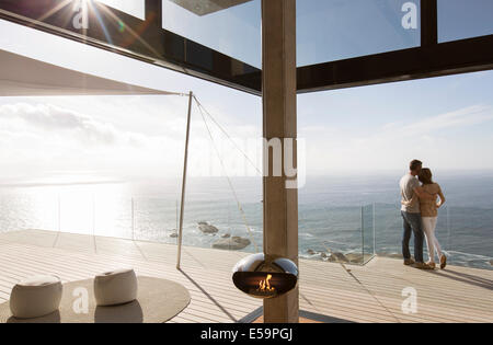 Couple standing on balcony of modern home - Stock Photo