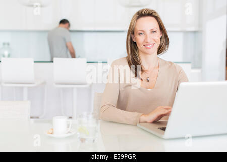 Woman using laptop at breakfast table - Stock Photo