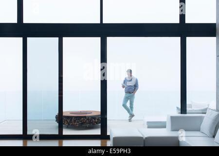 Man using cell phone on modern balcony - Stock Photo