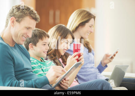 Family using technology on sofa - Stock Photo