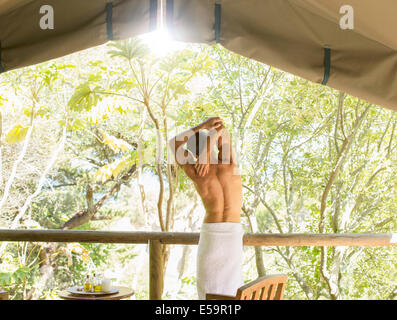 Man stretching in outdoor spa - Stock Photo