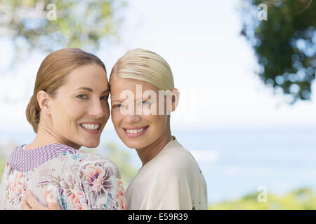Smiling women hugging indoors - Stock Photo