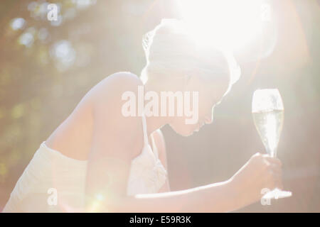 Woman drinking champagne outdoors - Stock Photo
