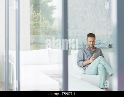 Man using digital tablet on sofa - Stock Photo