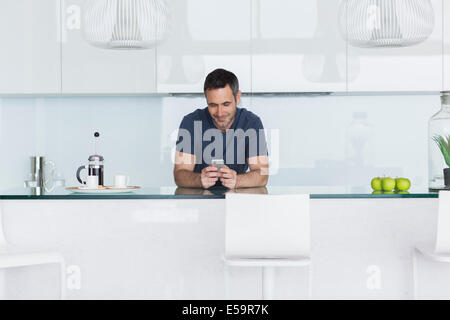Man using cell phone in modern kitchen - Stock Photo