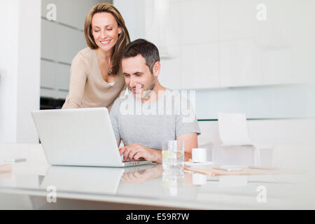 Couple using laptop at breakfast table - Stock Photo
