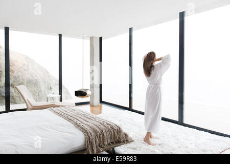 Woman wearing bathrobe in modern bedroom - Stock Photo