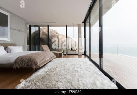 Shag rug and glass walls in modern bedroom - Stock Photo