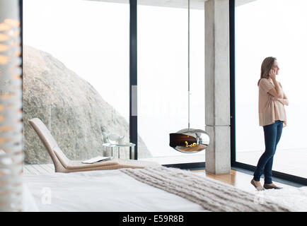Woman talking on cell phone in modern bedroom - Stock Photo