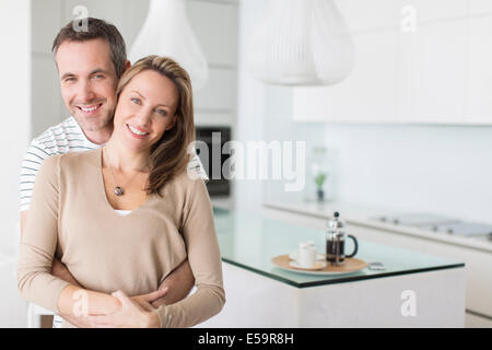 Couple hugging in modern kitchen - Stock Photo