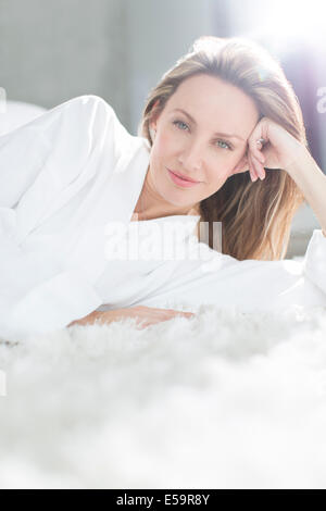 Woman in bathrobe laying on bed - Stock Photo
