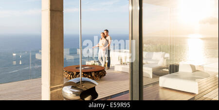 Couple on modern balcony overlooking ocean - Stock Photo