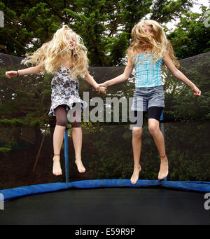 Girls jumping on trampoline outdoors - Stock Photo