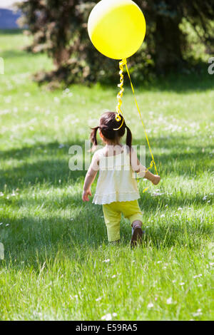 Girl carrying balloon in backyard - Stock Photo