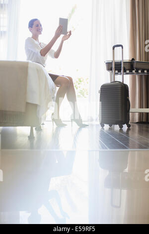Businesswoman using digital tablet in hotel room - Stock Photo
