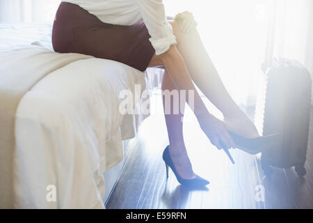 Businesswoman taking shoes off in hotel room - Stock Photo