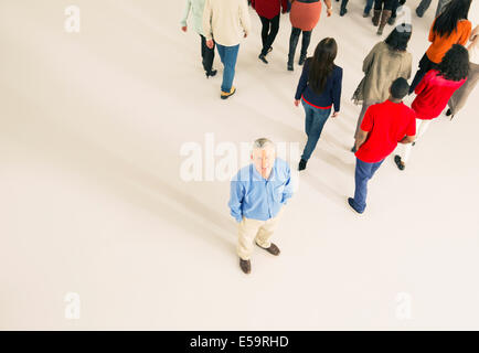 Crowd walking away from man - Stock Photo