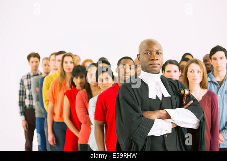 Serious judge in front of crowd - Stock Photo