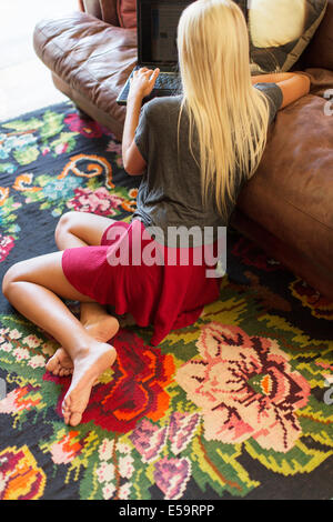 Woman using laptop in living room - Stock Photo