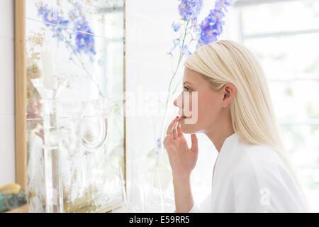 Woman admiring herself in bathroom mirror - Stock Photo