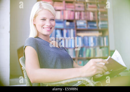 Woman reading in armchair - Stock Photo