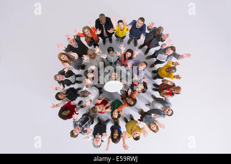 Portrait of business people in circle holding thought bubble - Stock Photo