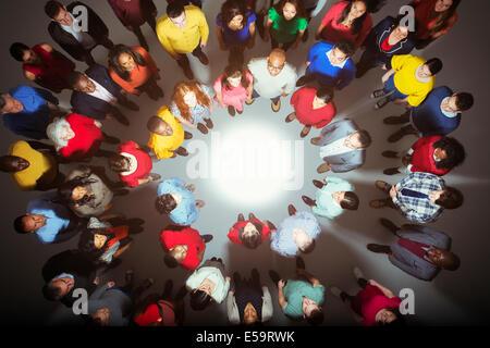 Diverse crowd standing around bright light - Stock Photo