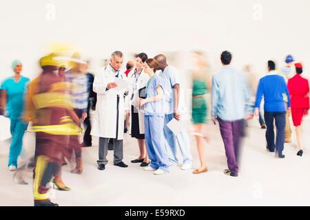 Workforce bustling around doctors and nurses - Stock Photo