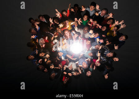 Diverse crowd cheering around bright light - Stock Photo