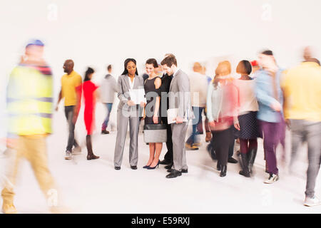 Bustling crowd around business people - Stock Photo
