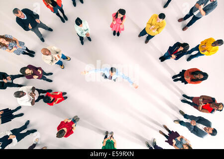 Crowd around businessman with arms outstretched - Stock Photo