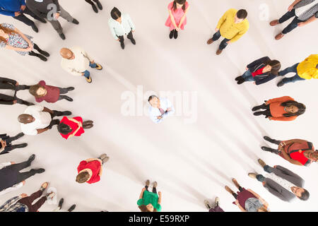 Crowd around businessman with arms crossed - Stock Photo