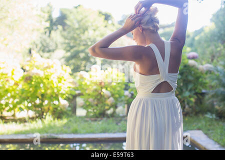 Woman tying up her hair outdoors - Stock Photo