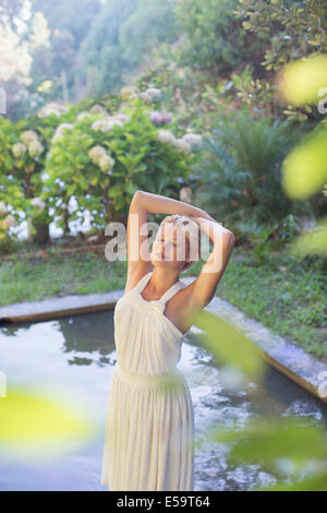Woman standing by pool outdoors - Stock Photo