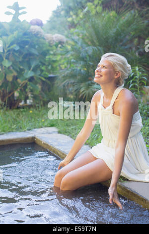 Woman dangling legs in pool - Stock Photo