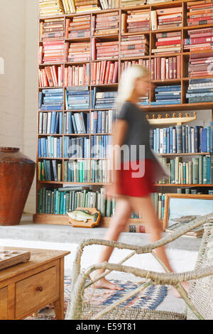 Blurred view of woman walking by bookcase - Stock Photo