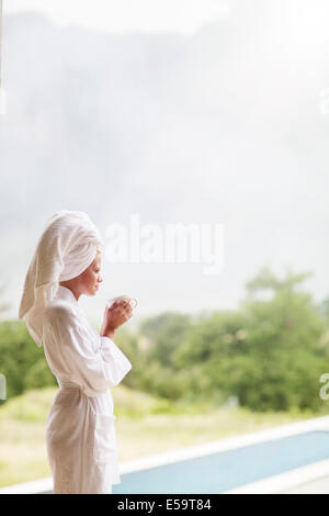 Woman in bathrobe drinking coffee outdoors - Stock Photo
