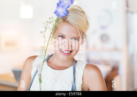 Woman holding flower in rustic kitchen - Stock Photo