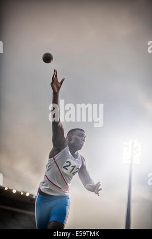 Track and field athlete throwing shot put - Stock Photo