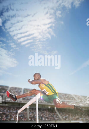 Track and field athlete jumping hurdle - Stock Photo