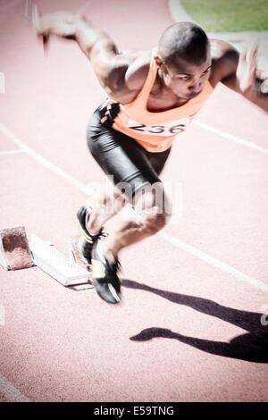 Runner taking off from starting block - Stock Photo