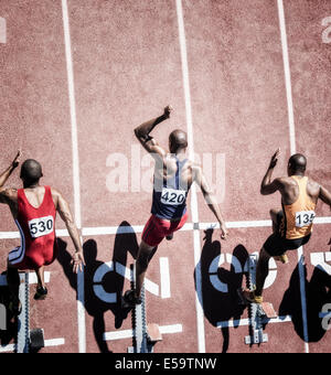 Sprinters taking off from starting block - Stock Photo