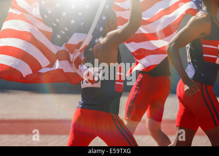 Track and field athletes holding American flags on track - Stock Photo