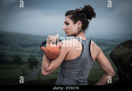 Woman with kettle bell practicing outdoor fitness - Stock Photo