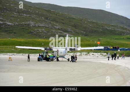 Passengers disembarking the aircraft which has just landed on the beach at Barra airport in the Outer Hebrides, - Stock Photo