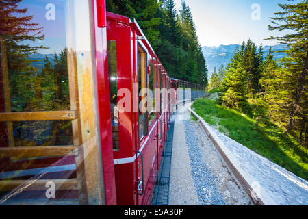 St. Wolfgang, Austria - August 6, 2013: Vintage train with red carriages cogwheel railway going to Schafberg Peak - Stock Photo