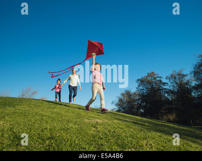 Mother and children flying kite in park - Stock Photo